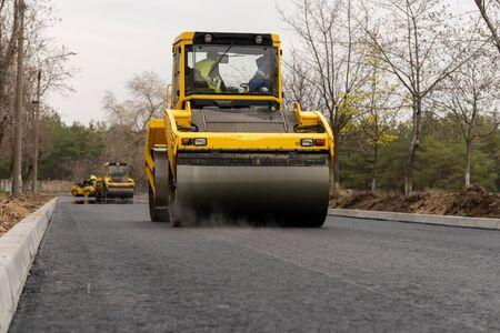 The vibratory roller levels the asphalt pavement.