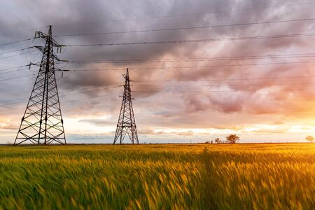 High-voltage power lines passing through a green field, on the background of a beautiful cloudy sky.