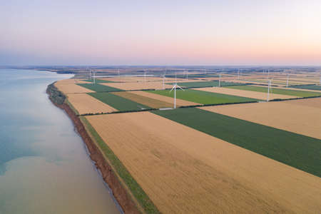 Sunset over the windmills. Wind turbines over fields of wheat and sunflowers. 免版税图像