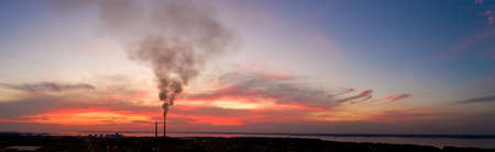 Panorama of an industrial landscape. Thermal power plant on a background of red sunset, aerial view. 免版税图像