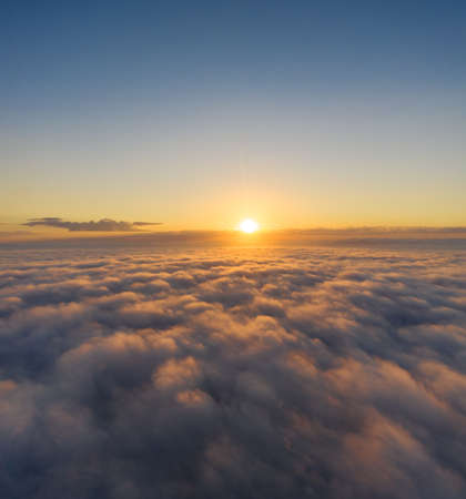 Beautiful sunrais cloudy sky from aerial view. Airplane view above clouds