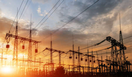High-voltage power lines at sunset or sunrise. High voltage electric transmission tower.