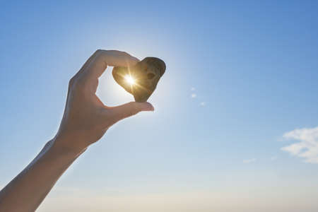 Sea stone in the shape of a heart in a woman's hand, against the background of the sky