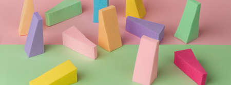 Top view of multi-colored sponges on different pastel-colored backgrounds. Abstract image.