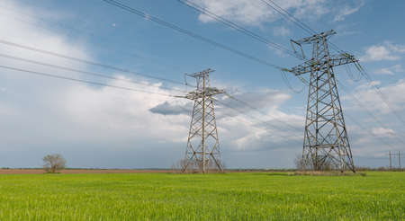 High voltage lines and pylons and a green agricultural landscape on a sunny day. Beautiful spring landscape of the European plain.