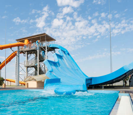 Water park, bright multi-colored slides with a pool. A water park without people on a summer day with a beautiful, cloudy blue sky. 新闻类图片