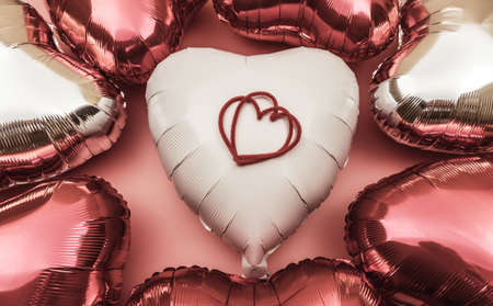 Heart-shaped balloon as a symbol of Valentine's Day. Background of foil balloons in the shape of a heart in shades of red.