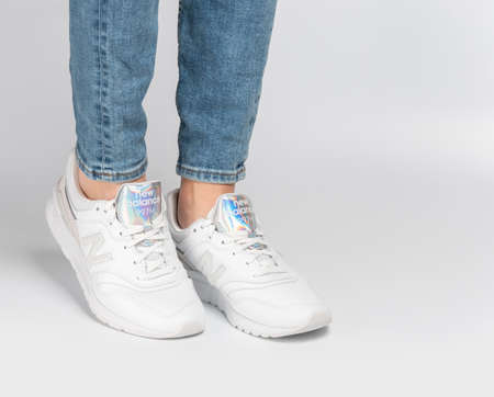 Kiev, Ukraine - January 03, 2021: White women's casual sneakers from New Balance brand on a light background. Young girl in jeans and sneakers on a gray background. Zdjęcie Seryjne - 162787985