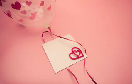Valentine's day card. Transparent balloon with hearts and a card on a ribbon. Top view background. Copyspace. 免版税图像