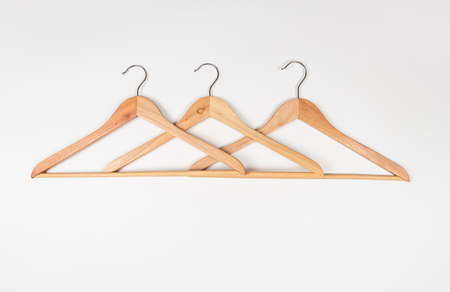 Clothes hangers made of wood on a light background. Hangers made of environmentally friendly material. 免版税图像