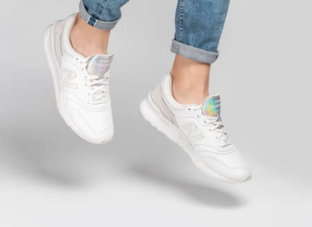 Kiev, Ukraine - January 03, 2021: White women's casual sneakers from New Balance brand on a light background. Young girl in jeans and sneakers on a gray background. 新闻类图片