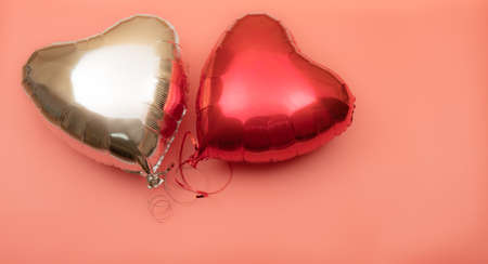 Two heart-shaped foil balloons on a pink background with place for text. Red and silver balloons on a light background.