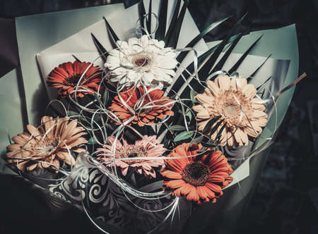 Beautiful bouquet of multicolored gerberas in cold pastel shades on a dark background. 免版税图像