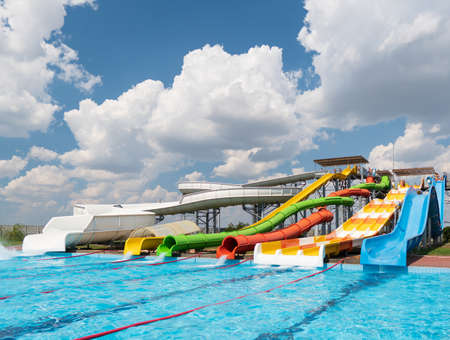 Water park, bright multi-colored slides with a pool. A water park without people on a summer day with a beautiful, cloudy blue sky. Zdjęcie Seryjne - 162284003
