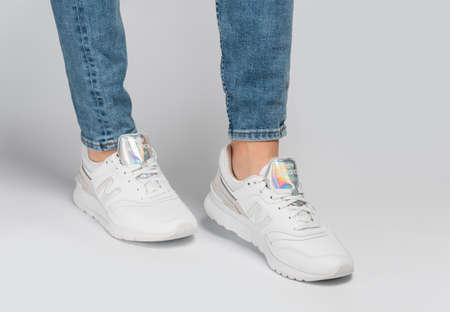 Kiev, Ukraine - January 03, 2021: White women's casual sneakers from New Balance brand on a light background. Young girl in jeans and sneakers on a gray background. Zdjęcie Seryjne - 162284008