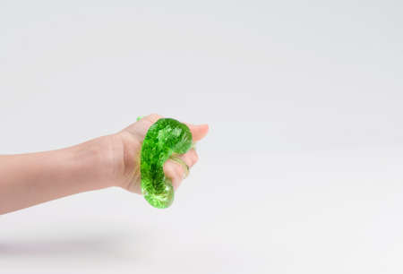 Toy slime in the hand of a child on a light background. The child plays with mucus and develops fine motor skills of the hands.