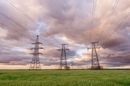 High-voltage power lines passing through a green field, on the background of a beautiful cloudy sky. Spring wallpapers.