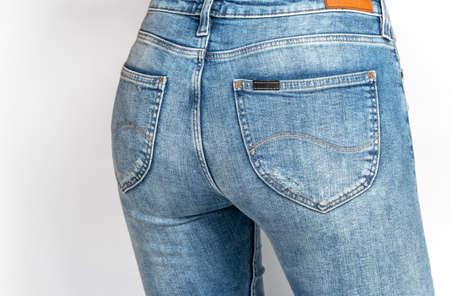 Women's ass in light blue jeans on a light background.