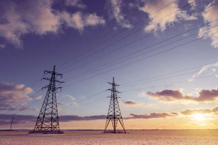 Electric poles in farm fields in winter. Transportation of alternative and renewable electricity. Standard-Bild