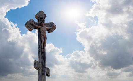 christian cross or crucifix in the rays of the sun against the background of a blue sky with clouds, a symbol of faith in god