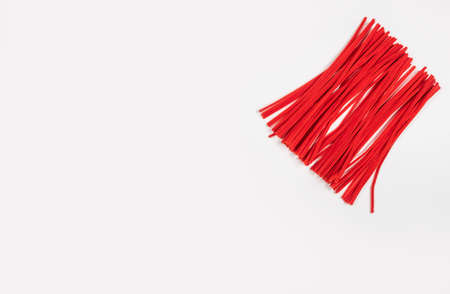 Red chenille wire on a light background. A lot of material for needlework. Place for text. Zdjęcie Seryjne
