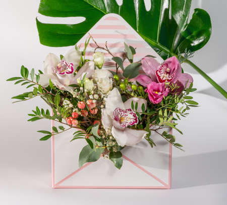 Delicate orchids in a gift box or basket on a light background. Bouquet of orchids, roses and chrysanthemums. Festive postcard.