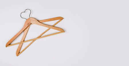 Clothes hangers made of wood on a light background. Hangers made of environmentally friendly material. Space for text.