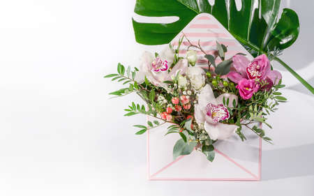 Bouquet of different flowers in an envelope-shaped gift box. Place for text. Delicate flowers as a gift for a woman or girl. Festive postcard.
