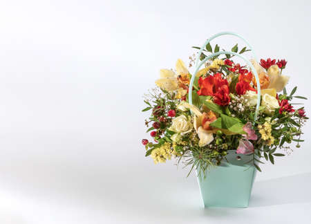 Delicate orchids in a gift box or basket on a light background. Space for text. Bouquet of orchids, roses and chrysanthemums. Festive postcard.