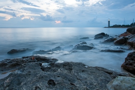 Beautiful sea coast with lighthouse at the sunset photo
