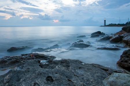 Prachtige zee kust met vuurtoren op de zonsondergang