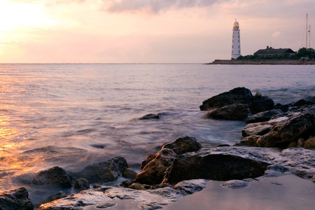 Beautiful rocky sea beach at the sunset with the lighthouse photo
