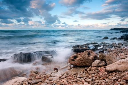 Belle plage de mer rocheux au coucher du soleil