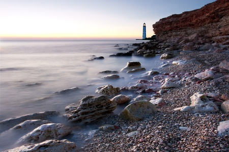 Beautiful sea beach with lighthouse and clear sky at the sunset photo