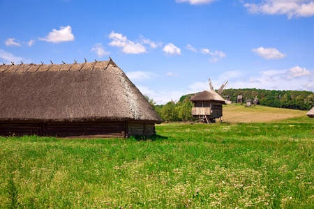 thatched house: Beautiful village landscape with wooden houses and windmills Stock Photo