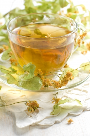 Linden tea in the transparent cup and dry linden flowers photo