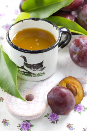 Plum juice and fresh fruits with leaves photo