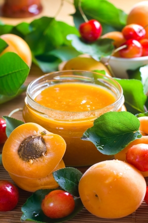 Apricot and sweet cherry jam in jar and fresh fruits with leaves photo