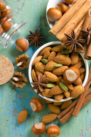 Aroma spices  Cinnamon, anise, peanuts, almonds, cardamom, hazelnuts on the vintage wooden surface  photo