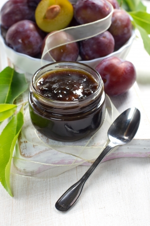 Plum jam in a glass jar and fresh fruits with leaves photo