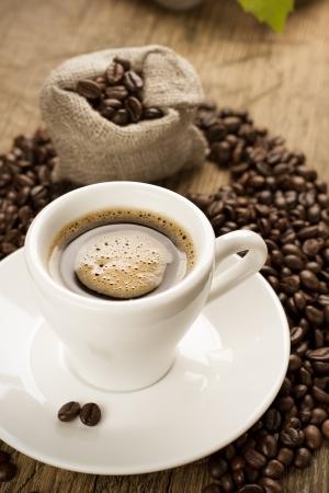 cafe colombiano: Pequeña taza de café negro sobre un fondo marrón con granos de café Foto de archivo