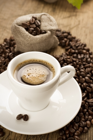 kopi: Small cup of black coffee on a brown background with coffee beans
