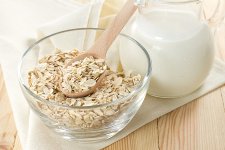 Oat flaks on a glass boel and jug of milk photo