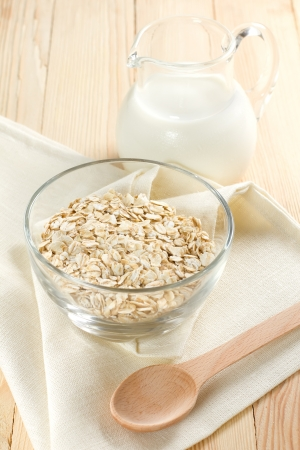 Oat flaks on a glass bowl and jug of milk photo