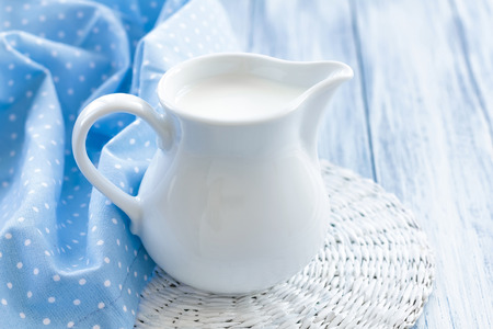 milk jugs: Milk jug on wooden table  Stock Photo