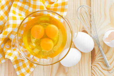 Raw eggs and whisk photo