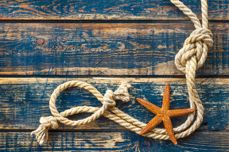 rough sea: wooden background with starfish and marine rope