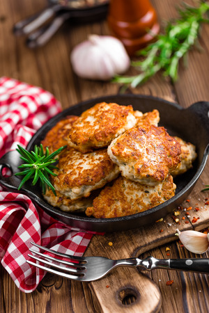 pan: meat cutlets in frying pan on wooden rustic table Stock Photo