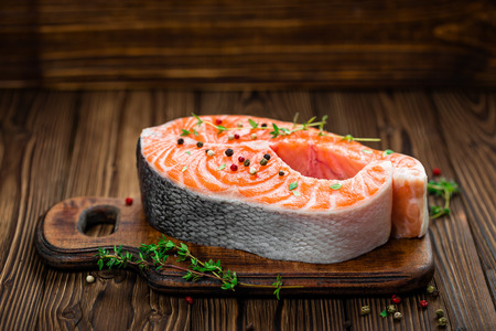 red pepper: raw salmon fish steak on wooden rustic background