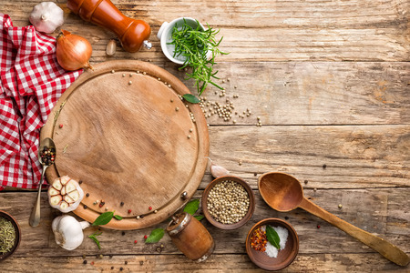 kulinarischen Hintergrund mit leeren Schneidebrett und Gewürzen auf Holztisch